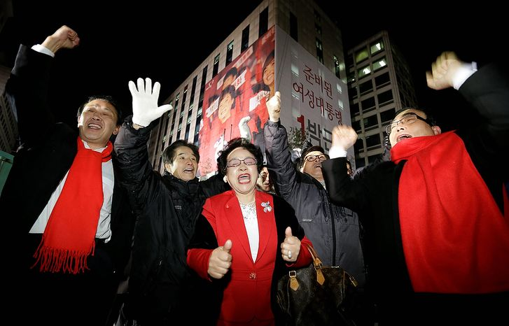Supporters of South Korean presidential candidate Park Geun-hye of the ruling Saenuri Party cheer near the party's head office in Seoul on Wednesday, Dec. 19, 2012. South Koreans voting for president Wednesday were almost evenly divided between Miss Park, the conservative daughter of a late dictator,