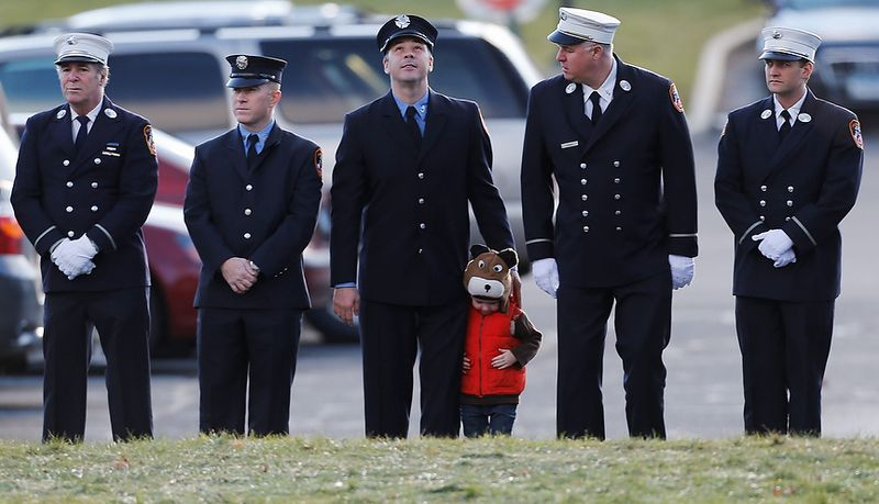 A child lines up with firefighters outside the funeral for school shooting victim Daniel Gerard Barden,at St. Rose of Lima Catholic Church in Newtown, Conn., Wednesday, Dec. 19, 2012.  According to firefighters, Daniel wanted to be a firefighter when he grew up and they honored hi