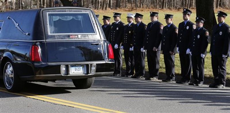 Firefighters stand as the procession heads to the cemetery outside the funeral for school shooting victim Daniel Gerard Barden at St. Rose of Lima Catholic Church in Newtown, Conn., Wednesday, Dec. 19, 2012. According to firefighters, Daniel wanted to be a firefighter when he grew up and they honored him at the service. Barden, 7, was killed when Ad