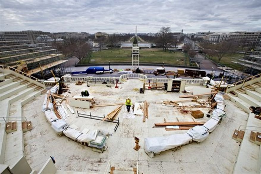Construction workers continue work on the platforms on the west side of the Capitol where dignitaries and news cameras will witness the inaugural ceremonies on Capitol Hill in Washington. The pomp surrounding the inauguration of the president can carry a hefty price tag, from the glitzy galas to all those inaugural balls. Think of it this way: It can cost about the same as 150 luxury Bentley cars, several dozen yachts or some $20 million shy of the cash needed for a Boeing 737 passenger jet. (AP Photo/J. Scott Applewhite, File)