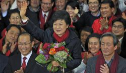 South Korean President-elect Park Geun-hye of the ruling Saenuri Party waves to supporters after arriving at party headquarters in Seoul on Wednesday, Dec. 19, 2012. (AP Photo/Kim Jae-hwan, Pool)