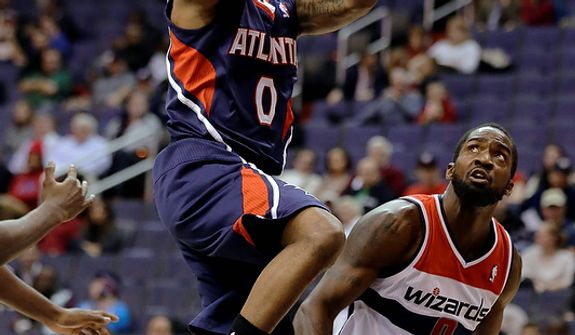 Atlanta Hawks guard Jeff Teague shoots over Washington Wizards forward Martell Webster in the first half of an NBA basketball game Tuesday, Dec. 18, 2012, in Washington. (AP Photo/Alex Brandon)