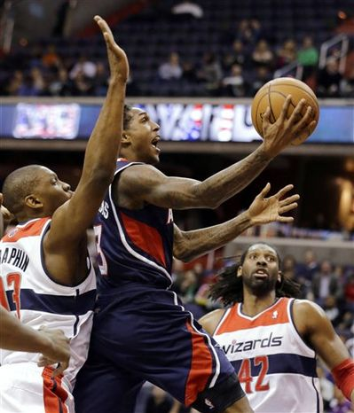 Atlanta Hawks guard Louis Williams shoots between Washington Wizards forward Kevin Seraphin (13), from France, and center Nene (42) from Brazil, in the first half of an NBA basketball game Tuesday, Dec. 18, 2012, in Washington. Williams had 24 points. The Hawks won 100-95 in overtime. (AP Photo/Alex Brandon)