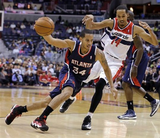 Atlanta Hawks guard Devin Harris drives around Washington Wizards guard Shaun Livingston in the first half of an NBA basketba