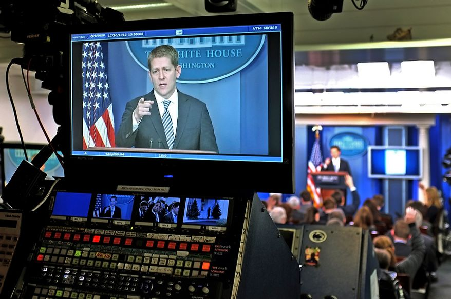 White House Press Secretary Jay Carney is seen on a television monitor in the Brady Briefing Room as he answers reporters questions during the daily press briefing at the White House in Washington, Thursday, Dec. 20, 2012. (AP Photo/J. David Ake)