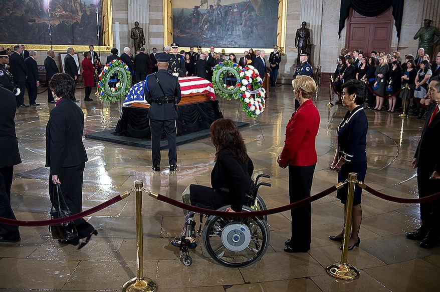 People, including U.S. Rep.-elect Tammy Duckworth, center, in the wheelchair, file past the casket of the late Sen. Daniel Inouye following a memorial service in the U.S. Capitol rotunda on Thursday, Dec. 20, 2012. Sen. Inouye, who served as a U.S. senator for 50 years, is only the 31st person to lie in state in the rotunda of the U.S. Capitol. It is seen as a sign of respect. (Barbara L. Salisbury/The Washington Times)
