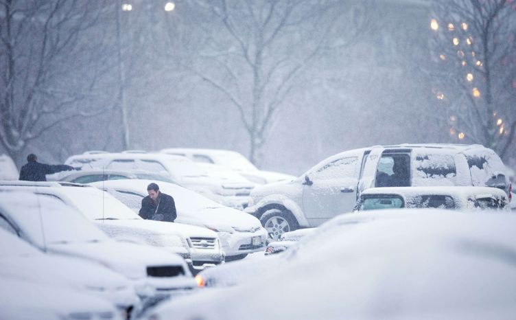 Mutual of Omaha employees clean their vehicles of snow before leaving on their drive home during the evening commute Wednesday Dec. 20, 2012, in Omaha Neb. A storm that has dumped more than a foot of snow in the Rocky Mountains is heading east and is forecast to bring the first major winter storm of the season to the central plains and Midwest. (AP Photo/The World-Herald, Matt Miller)