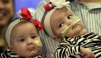 Shellie and Greg Tucker, parents of Allison, left and Amelia, present their 9-month-old girls who were formerly conjoined twins at Children's Hospital of Philadelphia (CHOP) Thursday, Dec. 20, 2012, in Philadelphia. Surgeons at CHOP separated the Tucker girls during a seven-hour operation in November. The infants from Adams, N.Y., had been joined at the lower chest and abdomen. They shared their chest wall, diaphragm, pericardium and liver. (AP Photo/Matt Rourke)