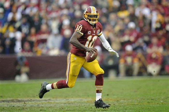 Washington Redskins quarterback Robert Griffin III scrambles with the ball during the second half of an NFL football game against the Baltimore Ravens in Landover, Md., Sunday, Dec. 9, 2012. (AP Photo/Ni