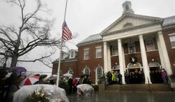 Officials including Connecticut Gov. Dan Malloy observe a moment of silence on the steps of Edmond Town Hall while bells ring 26 times in Newtown, Conn., Friday, Dec. 21, 2012. The chiming of bells reverberated throughout Newtown, commemorating one week since the crackle of gunfire in a schoolhouse killed 20 children and six adults in a massacre that has shaken the community and the nation. (AP Photo/Seth Wenig)