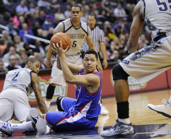 American guard Blake Jolivette, center, looks to pass against Georgetown forward Greg Whittington (2), Markel Starks (5) and Jabril Trawick, right, during the first half of an NCAA college basketball game, Saturday, Dec. 22, 2012, in Washington. (AP Photo/Nick Wass)