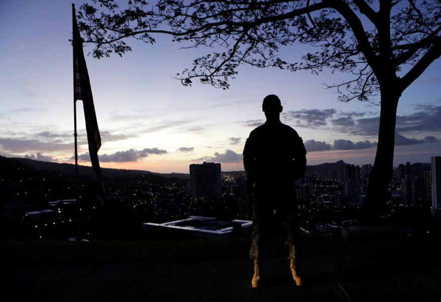 A Marine stands post at dawn prior to the Memorial Service for Sen. Daniel Inouye, D-Hawaii, at the Punchbowl National Memorial Cemetery of the Pacific in Honolulu, Sunday, Dec. 23, 2012. (AP Photo/Gerald Herbert)