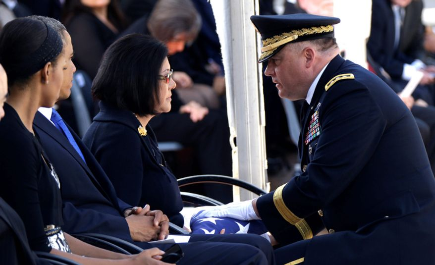 Lt. Gen. Francis Wiercinski, commander of the U.S. Army Pacific, presents an American flag to Irene Hirano Inouye, widow of Sen. Daniel Inouye, D-Hawaii, as she sits with President Barack Obama and first Lady Michelle Obama, left, during the memorial service for the late senator at the Punchbowl National Memorial Cemetery of the Pacific in Honolulu, Sunday, Dec. 23, 2012. Inouye, the first Japanese-American elected to both houses of Congress, died Dec. 17 at age 88. (AP Photo/Gerald Herbert)