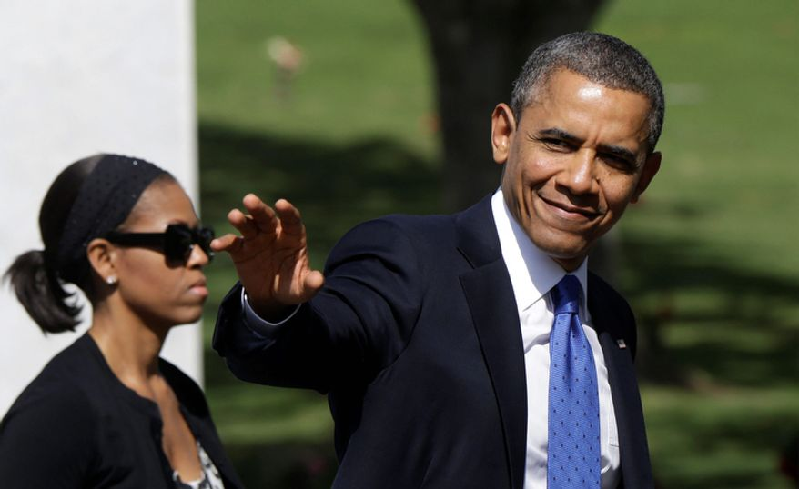 President Barack Obama waves as he leaves the Memorial Service for U.S. Sen. Daniel Inouye, D-Hawaii, with first lady Michelle Obama, at the Punchbowl National Memorial Cemetery of the Pacific in Honolulu, Sunday, Dec. 23, 2012. (AP Photo/Gerald Herbert)