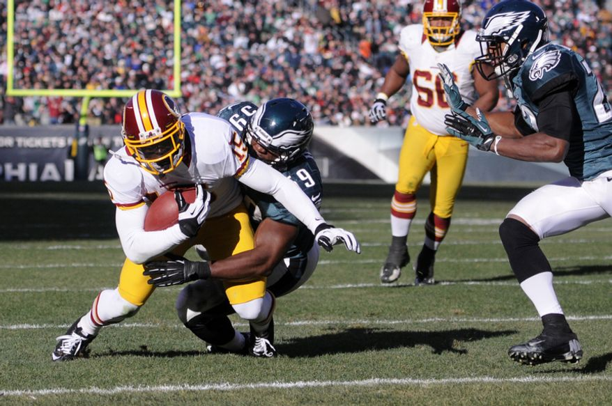 Washington Redskins wide receiver Josh Morgan (15) scores with Philadelphia Eagles middle linebacker DeMeco Ryans (59) on his back during the second quarter at Lincoln Financial Field, Philadelphia, Pa., Dec. 23, 2012. (Preston Keres/Special to The Washington Times)