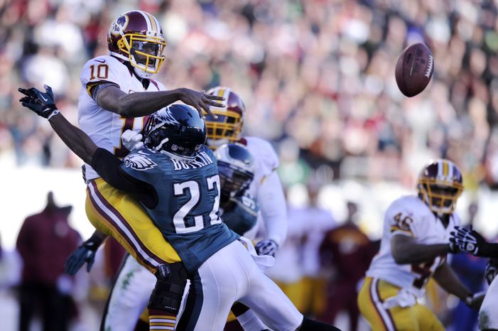 """Robert Griffin III (left) is experiencing """"no limited performance"""" because of his knee injury, Redskins coach Mike Shanahan said. (Preston Keres/Special to The Washington Times)"""