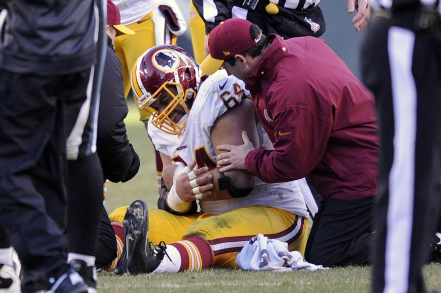 Washington Redskins defensive tackle Kedric Golston (64) sits on the ground after injuring his arm in the fourth quarter at Lincoln Financial Field, Philadelphia, Pa., Dec. 23, 2012. (Preston Keres/Special to The Washington Times)