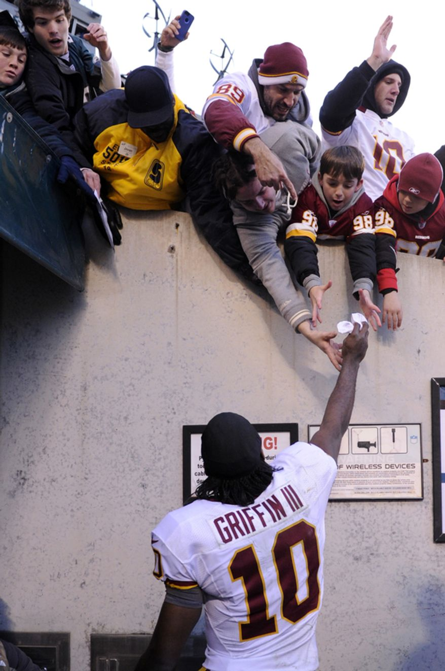 Washington Redskins quarterback Robert Griffin III (10) gives his arm sleeve to the fans as he leave the field Lincoln Financial Field, Philadelphia, Pa., Dec. 23, 2012. (Preston Keres/Special to The Washington Times)