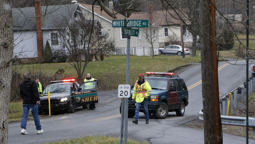 Emergency responders block Juniata Valley Road on Friday, Dec. 21, 2012, in Geeseytown, Pa., after a man fatally shot a woman decorating for a children's Christmas party at a tiny church hall and killed two men elsewhere in the rural central Pennsylvania township before he was fatally shot in a gunfight with state troopers. (AP Photo/Keith Srakocic)