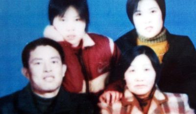 Chinese Christian preacher Gong Shengliang (bottom left) is seen with unidentified family members in an undated photograph. Relatives and two of his followers are seeking his release from prison after he apparently suffered a stroke.(Associated Press)