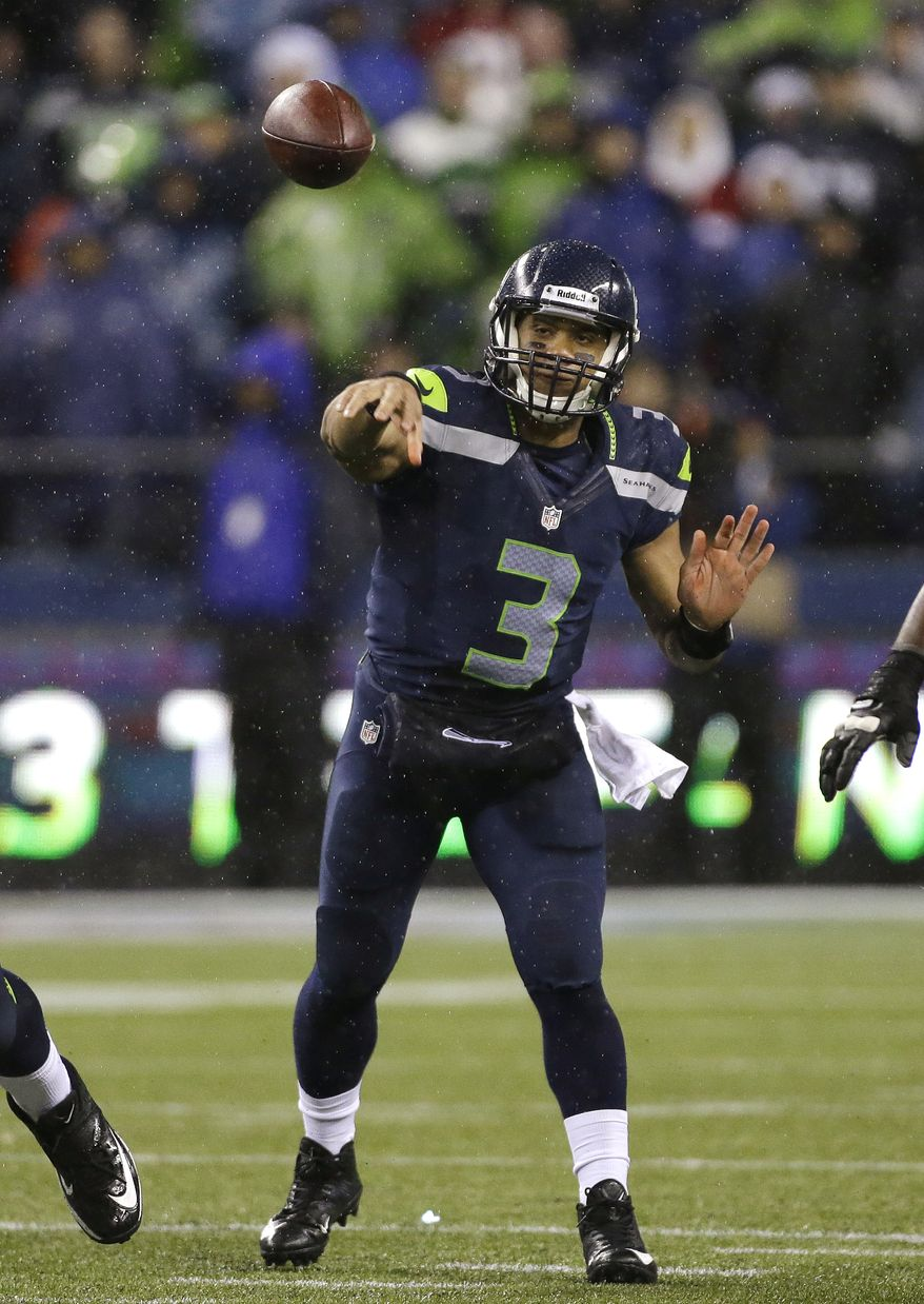 Seattle Seahawks quarterback Russell Wilson throws against the San Francisco 49ers in the first half of an NFL football game, Sunday, Dec. 23, 2012, in Seattle. (AP Photo/Elaine Thompson)