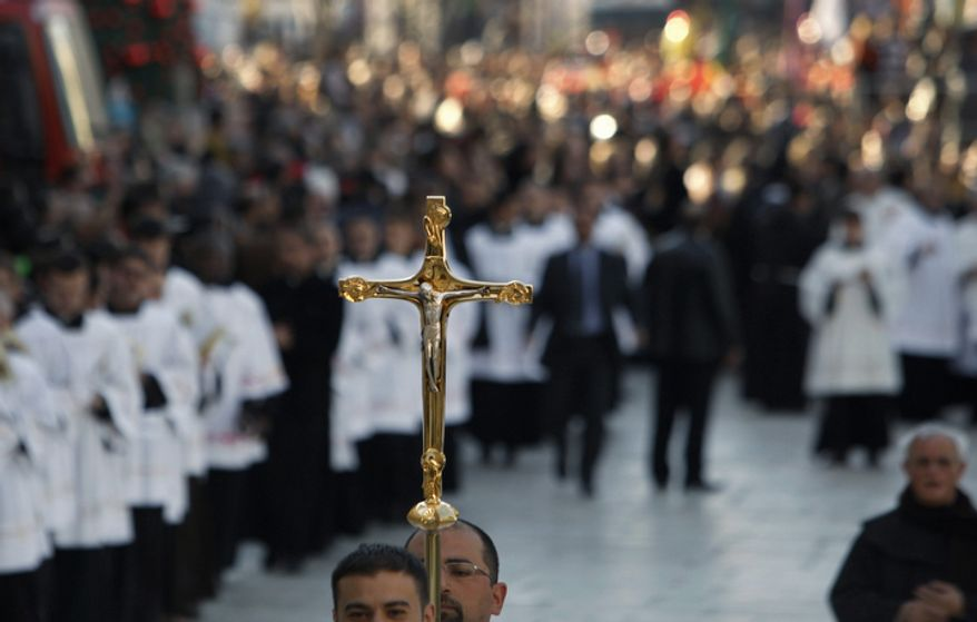 A cross is held during Christmas celebrations outside the Church of Nativity, traditionally believed by Christians to be the birthplace of Jesus Christ, in the West Bank town of Bethlehem, Monday, Dec. 24, 2012. Thousands of Christian worshippers and tourists arrived in Bethlehem on Monday to mark Christmas at the site where many believe Jesus Christ was born. (AP Photo/Adel Hana)