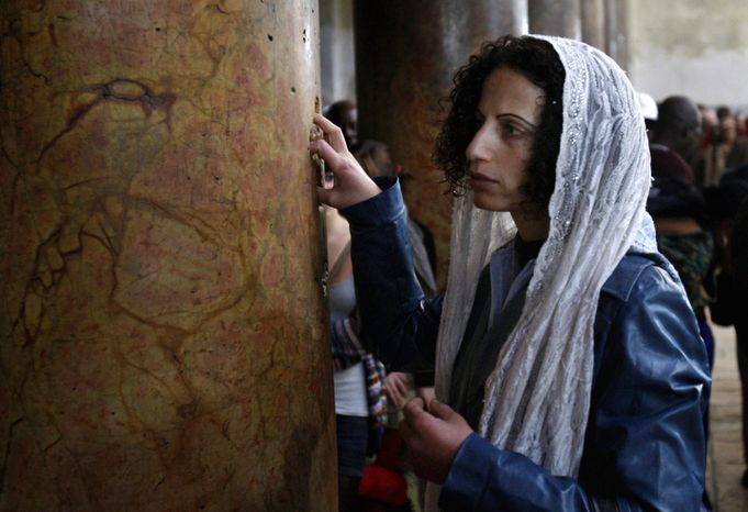 A Catholic pilgrim touches a column inside the Church of the Nativity, traditionally believed by Christians to be the birthplace of Jesus Christ, in the West Bank town of Bethlehem. (AP Photo/Adel Hana)