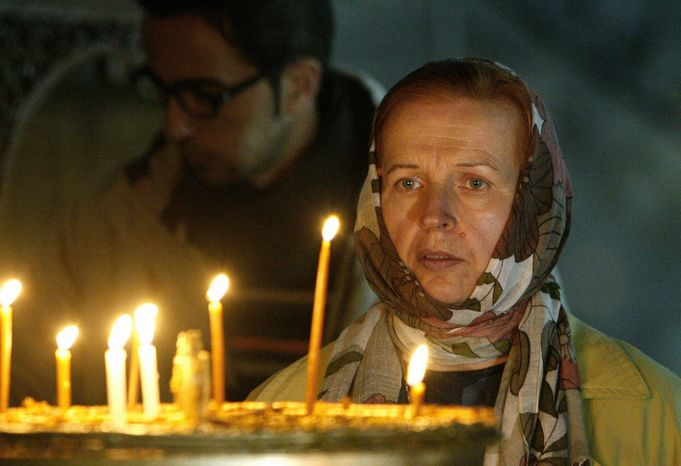 A Catholic pilgrim looks at lit candles outside of the Grotto at the Church of Nativity, traditionally believed by Christians to be the birthplace of Jesus Christ, in the West Bank town of Bethlehem,