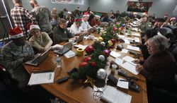Volunteers take phone calls from children asking where Santa is and when he will deliver presents to their house during the annual NORAD Tracks Santa Operation at the North American Aerospace Defense Command (NORAD) at Peterson Air Force Base in Colorado Springs, Colo., on Monday Dec. 24, 2012. More than a thousand volunteers at NORAD handle more than 100,000 thousand phone calls from children around the world every Christmas Eve, with NORAD continually projecting Santa's supposed progress delivering presents. (AP Photo/Brennan Linsley)