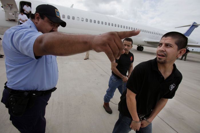 **FILE** Shackled Mexican immigrants are directed by a guard for deportation by U.S. Immigration and Customs Enforcement in Harlingen, Texas, on May 25, 2010. (Associated Press)