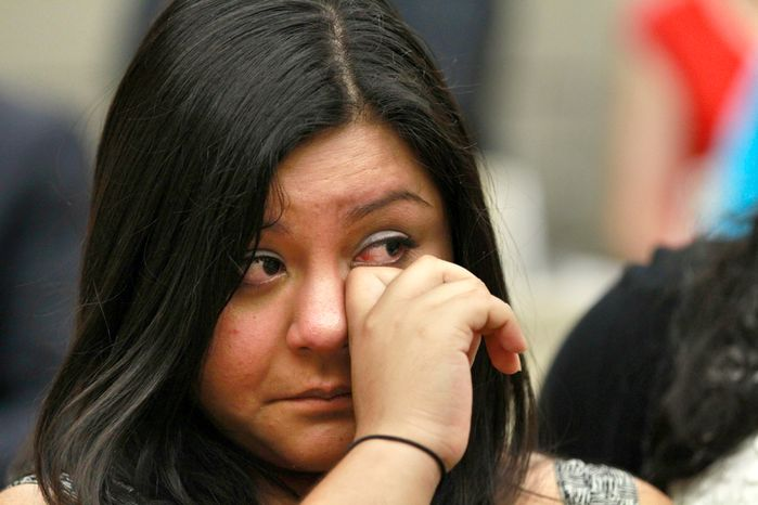 Myrna Orozco, 22, of Kansas City, Mo., an illegal immigrant originally from Mexico, wipes away tears on Friday, June 15, 2012, in Washington while watching President Obama announce that the U.S. government will stop deporting and begin granting work permits to younger illegal immigrants
