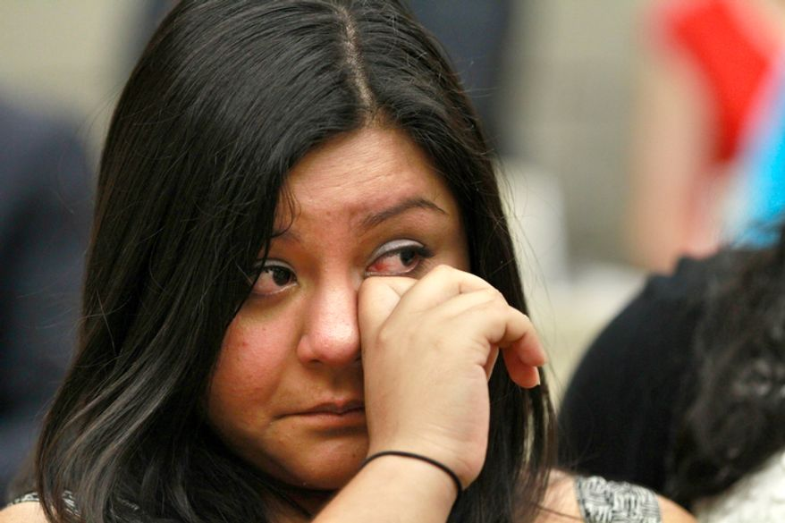 Myrna Orozco, 22, of Kansas City, Mo., an illegal immigrant originally from Mexico, wipes away tears on Friday, June 15, 2012, in Washington while watching President Obama announce that the U.S. government will stop deporting and begin granting work permits to younger illegal immigrants who came to the U.S. as children and have since led law-abiding lives. (AP Photo/Jacquelyn Martin)