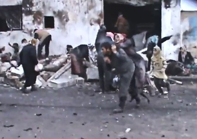 This Sunday, Dec. 23, 2012, image taken from video that has been authenticated based on its contents and other AP reporting shows a Syrian man carrying an elderly woman after a government airstrike hit the Hama suburb of Halfaya, Syria. (AP Photo/Shaam News Network via AP video)