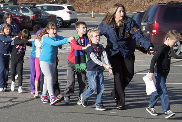 Connecticut State Police lead children from the Sandy Hook Elementary School in Newtown, Conn., following the shooting there on Friday, Dec. 14, 2012. (AP Photo/Newtown Bee, Shannon Hicks)