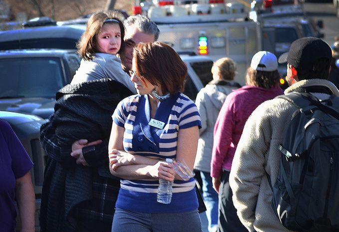 A young girl is comforted following the mass shooting at the Sandy Hook Elementary School in Newtown, Conn., about 60 miles northeast of New York, on Friday, Dec. 14, 2012. (AP Photo/The New Haven Register, Melanie Stengel)