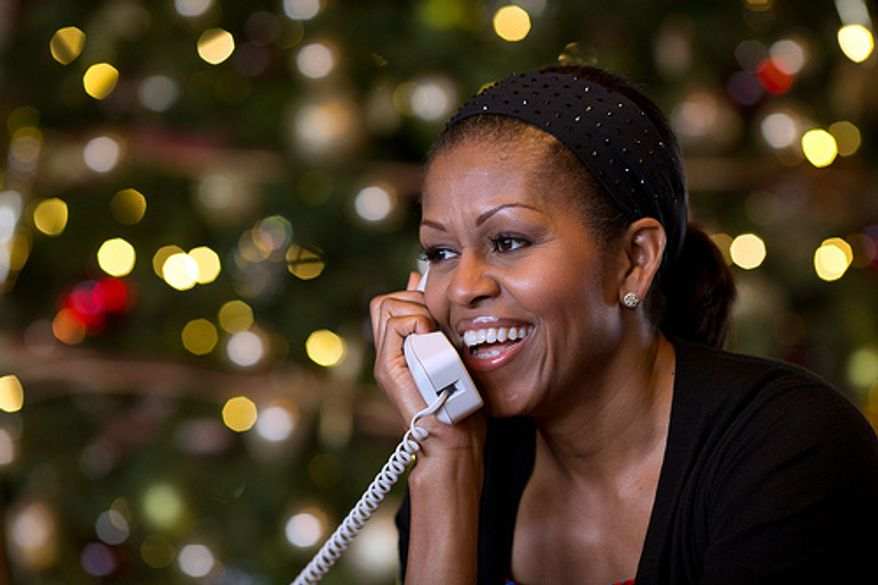 First Lady Michelle Obama reacts while talking on the phone to children across the country as part of the annual NORAD Tracks Santa program. Mrs. Obama answered the phone calls from Kailua, Hawaii, Christmas Eve, Dec. 24, 2012. (Official White House Photo by Pete Souza)