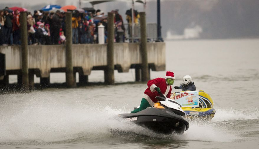 The Grinch speeds along the water in a jet ski during the 27th annual show of The Water-Skiing Santa.  (Rod Lamkey Jr./The Washington Times)