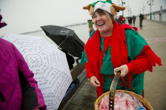An elf offers free candy canes to people during the 27th annual show of The Water-Skiing Santa on the Potomac River in National Harbor, Md., Monday, Dec. 24, 2012.  (Rod Lamkey Jr./The Washington Times)