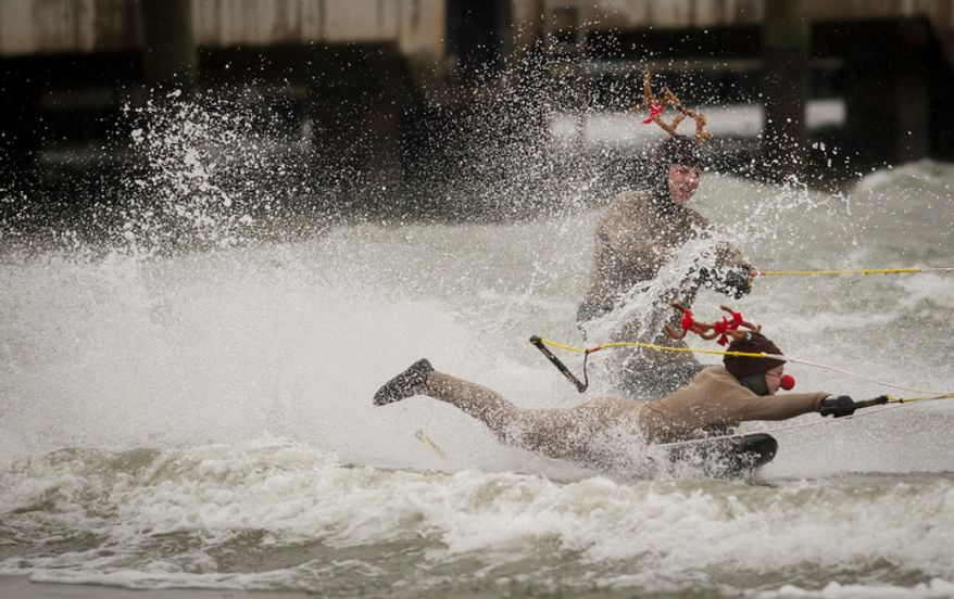 Dressed as reindeer, a man and a woman take to the water on water skis during the 27th annual show of The Water-Skiing Santa.  (Rod Lamkey Jr./The Washington Times)