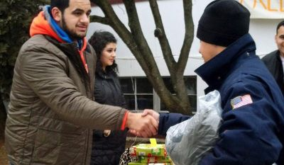 In this photo provided by Sportstars, football player Oday Aboushi, left, helps distribute presents to people affected by Superstorm Sandy in the Staten Island borough of New York, Saturday, Dec. 22, 2012. Aboushi, an NCAA college football offensive lineman from Virginia and potential first-round pick in the NFL draft, returned to a neighborhood he once hung out in while growing up in New York to lend a hand to nearly 1,000 residents in need of food, clothing and supplies. (AP Photo/Sportstars, Emil Boccio)