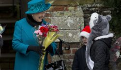 ** FILE ** Britain's Queen Elizabeth II receives flowers from children after attending the royal family's traditional Christmas Day church service in Sandringham, England, on Tuesday, Dec. 25, 2012. (AP Photo/Matt Dunham)