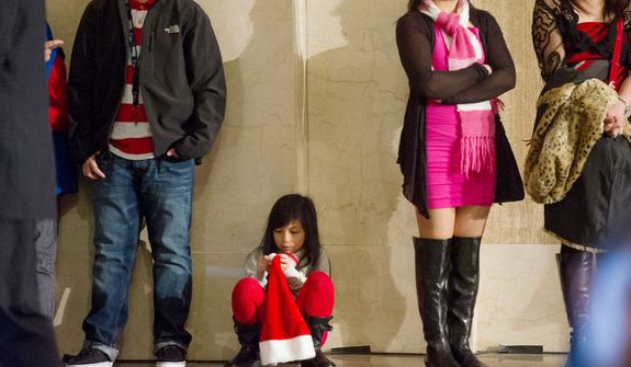 Jasmine Garcia, 6, of Bladensburg, Md., plays with a santa hat as she and other church goers wait for Archbishop of Washington Cardinal Donald Wuerl to lead a congregation of 4,000 in Solemn Mass of Christmas Day . (Andrew Harnik/The Washington Times)