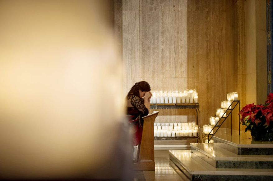 Rachel Acol, of Hyattsville, Md., prays before the Solemn Mass of Christmas Day at the Basilica of the National Shrine of the Immaculate Conception. (Andrew Harnik/The Washington Times)