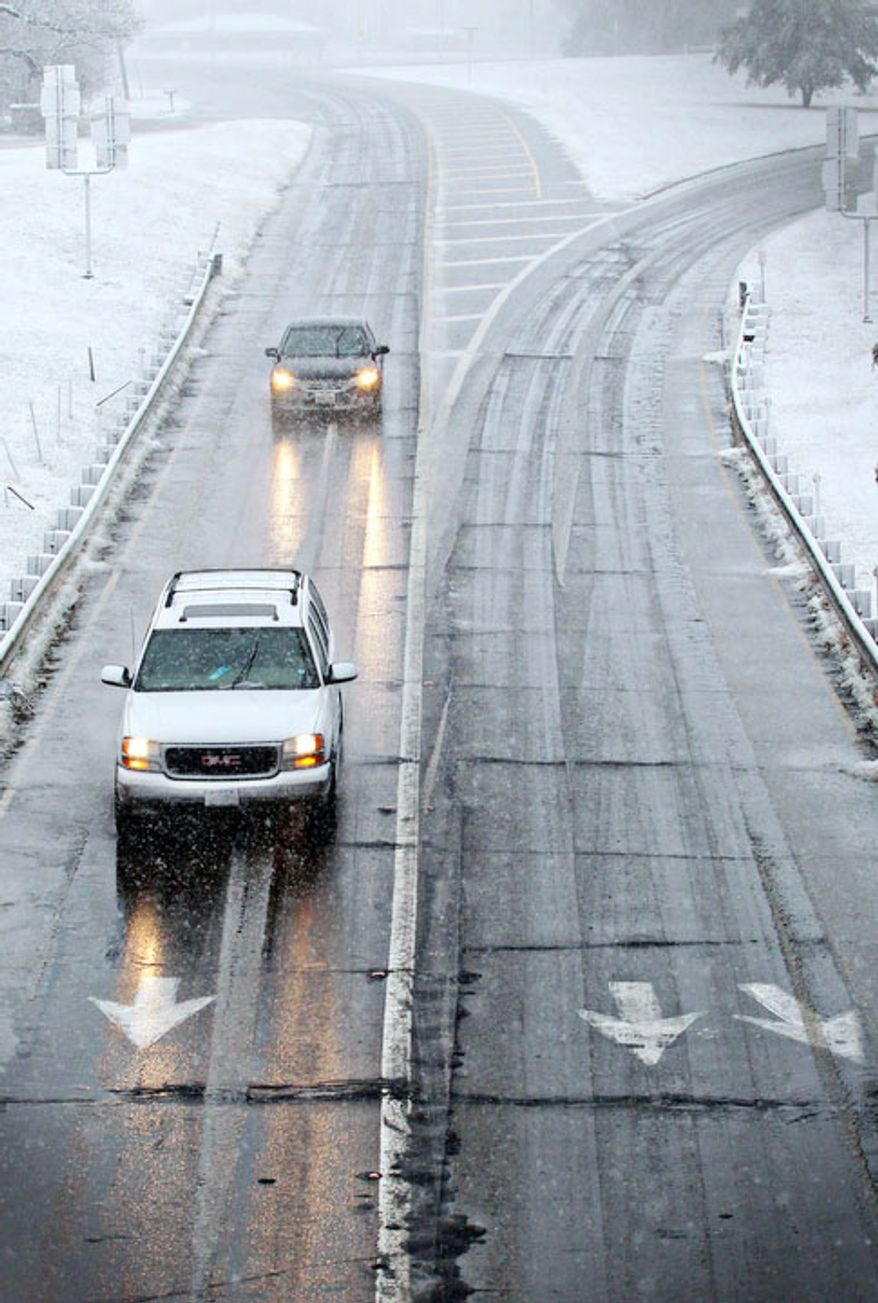 Drivers maneuver wet and icy roads in Paris, Texas Tuesday, Dec. 25, 2012 after a strong winter system dropped inches of rain and snow on most of North East Texas. (AP Photo/The Paris News, Sam Craft)