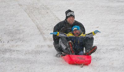 Lucas Martinez  and his dad, Nick Martinez hit the hill at Trinity Park in Fort Worth, Texas for Christmas Day fun in the snow Tuesday, Dec. 25, 2012. (AP Photo/The Fort Worth Star-Telegram, Ben Noey Jr.)
