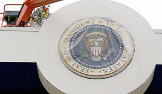 A painter touches up the presidential viewing stand in front of the White House in Washington on Thursday, Dec. 20, 2012, as preparations continue for the Inauguration on Monday, Jan. 21, 2013. (AP Photo/J. David Ake)