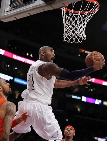 Los Angeles Lakers guard Kobe Bryant (24) shoots a reverse lay up between New York Knicks center Tyson Chandler, left, and forward Carmelo Anthony, right, during the first half of their NBA basketball game in Los Angeles, Tuesday, Dec. 25, 2012. (AP Photo/Alex Gallardo)