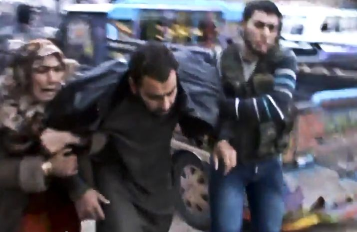 Syrians help a wounded man after a government airstrike hit the Hama suburb of Halfaya, Syria, on Sunday, Dec. 23, 2012, in this image taken from video that has been authenticated based on its contents and other AP reporting. (AP Photo/Shaam News Network via AP video)
