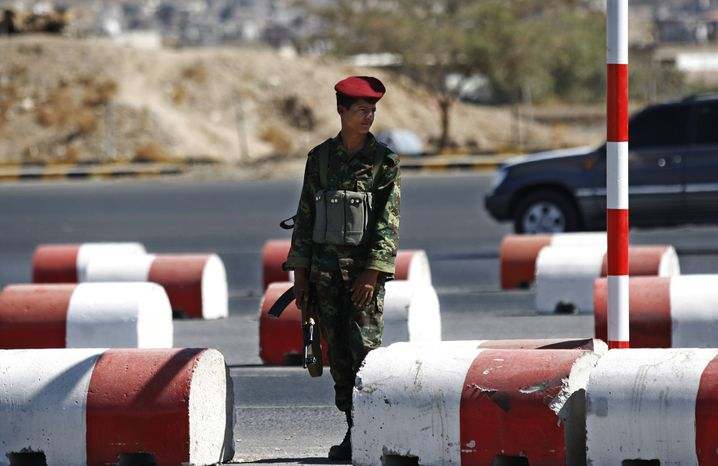 A Yemeni soldier stands guard at a street leading to the presidential palace in Sanaa, Yemen, on Tuesday, Dec. 25, 2012. Gunmen on motorbikes assassinated two Yemeni army officers in Sanaa, the capital, while clashes between the military and tribal fighters loyal to al Qaeda in a northeastern province killed three soldiers and several tribesmen, officials said. (AP Photo/Hani Mohammed)