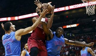 Oklahoma City Thunder's Thabo Sefolosha (2) and Kendrick Perkins (5) defend Miami Heat's Chris Bosh (1) during the first half of an NBA game, Tuesday, Dec. 25, 2012, in Miami. (AP Photo/J Pat Carter)
